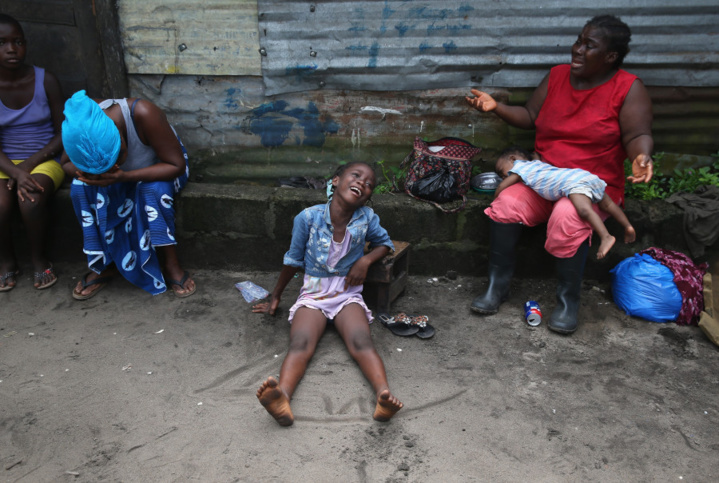 Sophia Doe (R), et ses petites-filles Arthuneh Qunoh (C), 9 et Beauté Mandi, 9 mois (2e R) en pleurs à l'arrivée d'une équipe de sépulture Ebola, qui est venue récupérer la dépouille de sa sœur morte d'Ebola, pour la crémation, le 10 Octobre 2014 à Monrovia, au Libéria. (John Moore / Getty Images)