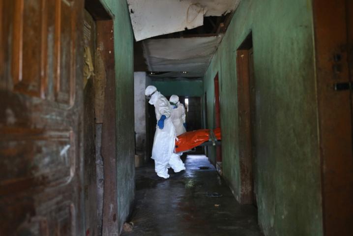 Une équipe de sépulture Ebola, vêtue de vêtements de protection, porte le corps d'une femme, 54 ans, de la chambre où elle est décédée dans la banlieue de New Kru ville le 10 Octobre 2014 à Monrovia, au Libéria. (John Moore / Getty Images)