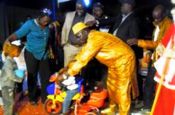 Le directeur Ibrahima DIAO remet un cadeau à un enfant du personnel, en présence de Masseck NGOM et Birima NDIAYE