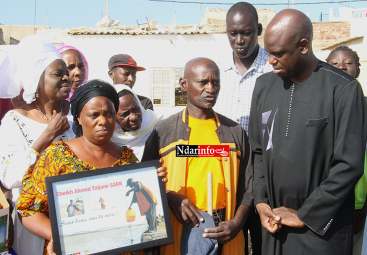 L'èpouse de M. SARR tenant le diplome d'honneur de NDARINFO