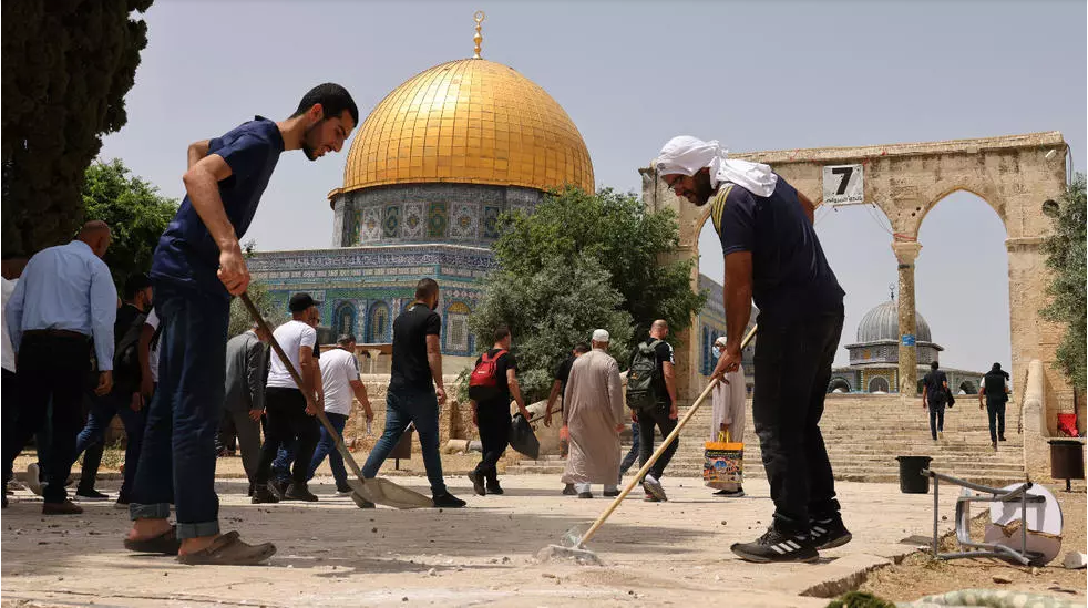 Des Palestiniens nettoient l'esplanade des Mosquées à Jérusalem, le 10 mai 2021, après de nouveaux affrontements avec des policiers israéliens. © Ahmad Gharabli, AFP