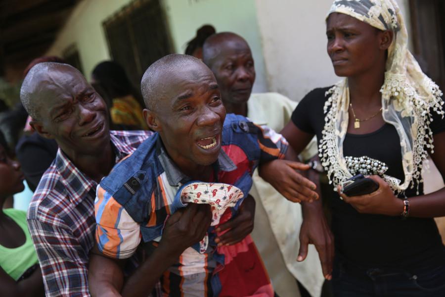 Cet homme pleure de toutes ses larmes à la vue de l'équipe de sépulture Ebola venue récupérer le corps de sa femme pour la crémation (John Moore / Getty Images)