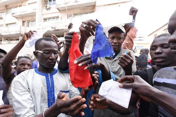 Des manifestants sénégalais brûlent un drapeau français, le 16 janvier 2015 à Dakar, pour protester contre la publication d'une caricature de Mahomet par Charlie Hebdo (Photo Seyllou. AFP)