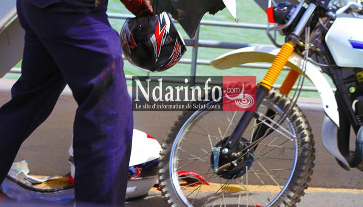 Un policier récupère le casque et les restes de la moto. Crédit Photo: NdarInfo
