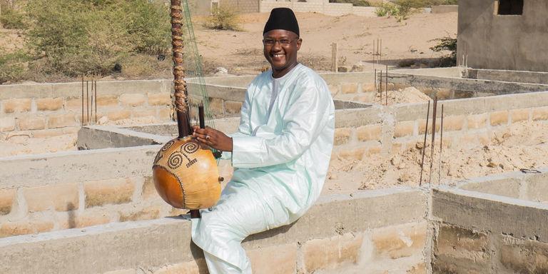 Ablaye Cissoko, ici en juin 2015 sur l'emplacement de sa future école de kora, près de Saint-Louis, au Sénégal. Crédits : Youri Lenquette
