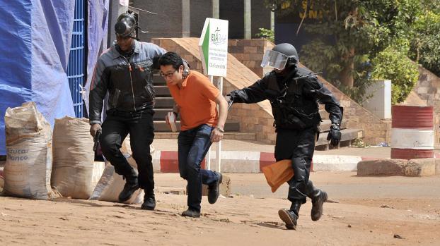 Un otage évacué de l'hôtel Radisson Blu par les forces de sécurité maliennes, à Bamako, le 20 novembre 2015.  (HABIBOU KOUYATE / ANADOLU AGENCY / AFP)