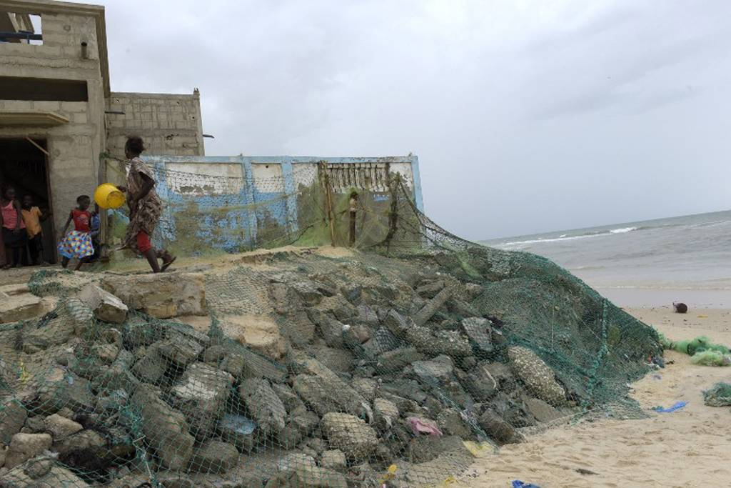 Wave breakers are used to protect houses in the Gokhou Mbathe district against the approaching sea. AFP PHOTO / SEYLLOU