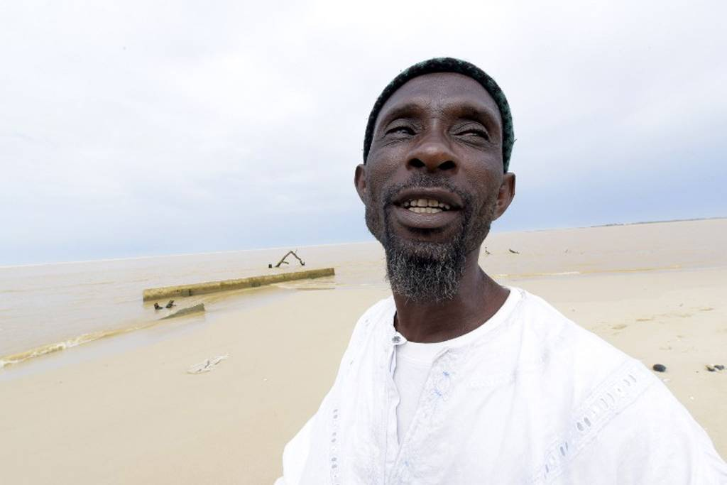 52-year-old Ameth Sene Diagne, chief of the Doune Baba Dieye village, describes how his village looked like before it was swallowed by the sea, on October 26, 2015, in Saint-Louis du Sénégal. AFP PHOTO / SEYLLOU
