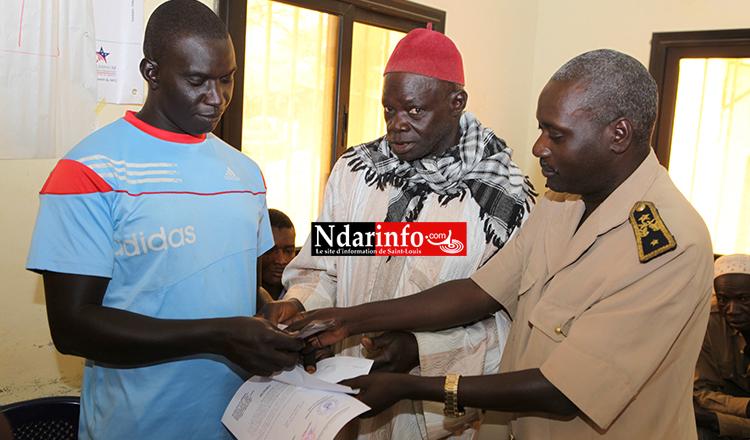 Le Sous Préfet Ibrahima NDAO remet une enveloppe à un homme qui a perdu sa femme au cours du naufrage.